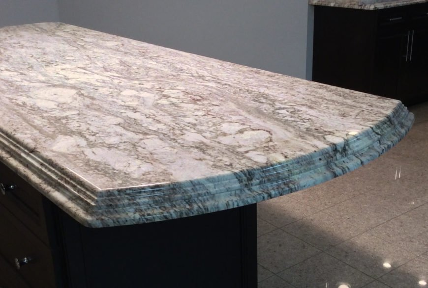 A beautiful white granite with gray veining and a custom stacked edge. This is just one of several incredible edge designs.
