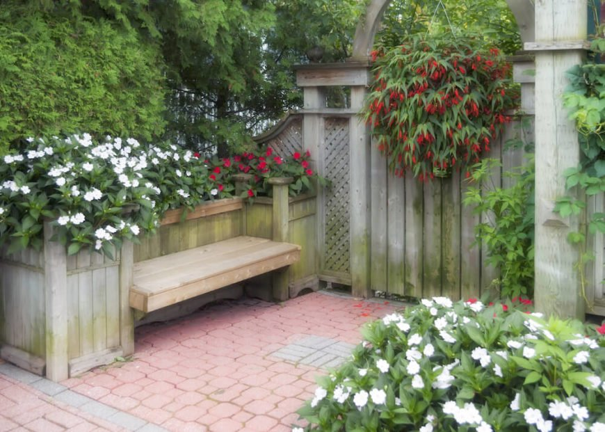 Here is a fantastic example of a bench being built into other features. This bench is built in the middle of some raised flower beds. This makes great use of space that may have otherwise gone unused.