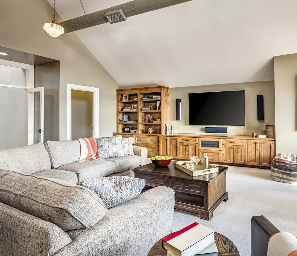 Built-in bookcases and hiding drawers in the coffee table are great ways to take advantage of wall and floor space for organizational purposes.