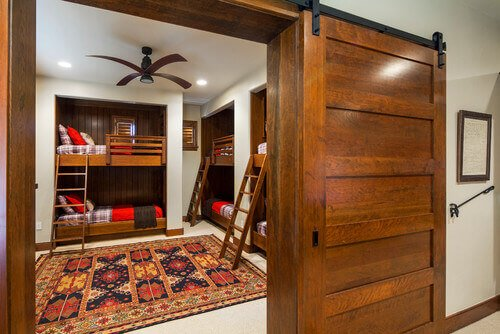 Sliding barn doors can never be slammed, and typically do not have locks. That means that a breeze won't cause slamming doors during the spring and summer. This door leads into a bunk room.