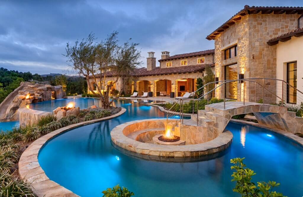 In the center of this pool is a fire pit that allows for a cookout or a fun hang out spot by the fire. When the swimming is done and you need to dry off, this is the perfect place for it. The bridge over the pool makes sure that you can stay dry and get to the fire.