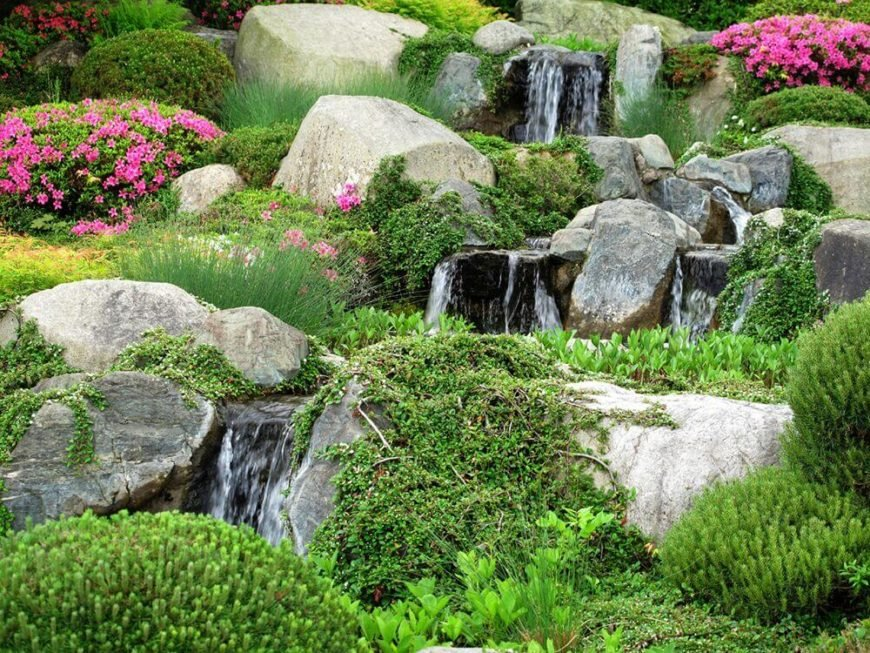 A water feature alongside wild moss and vines gives a rock garden a stunning natural feel. By leaving the rocks unattended you have a chance of cultivating an appeal like this.