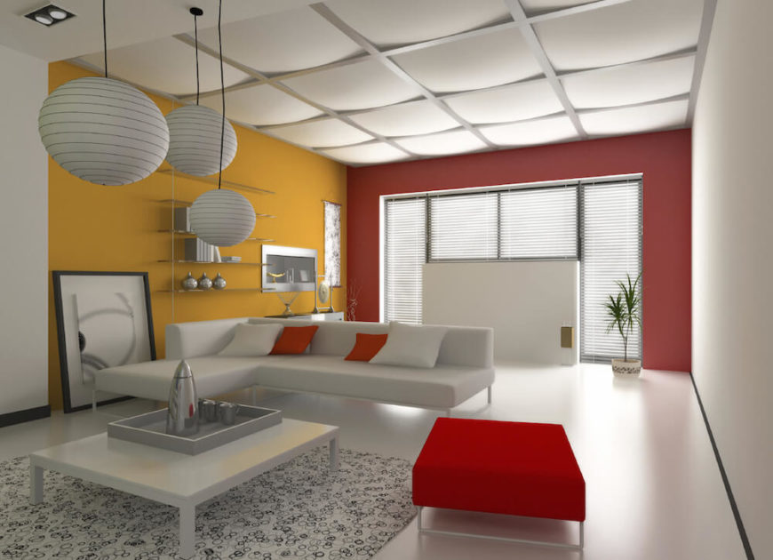 This modern living room features a drop ceiling, which adds texture and interest to the otherwise straight, geometric lines of the space. Bold splashes of marigold and crimson brighten the space.