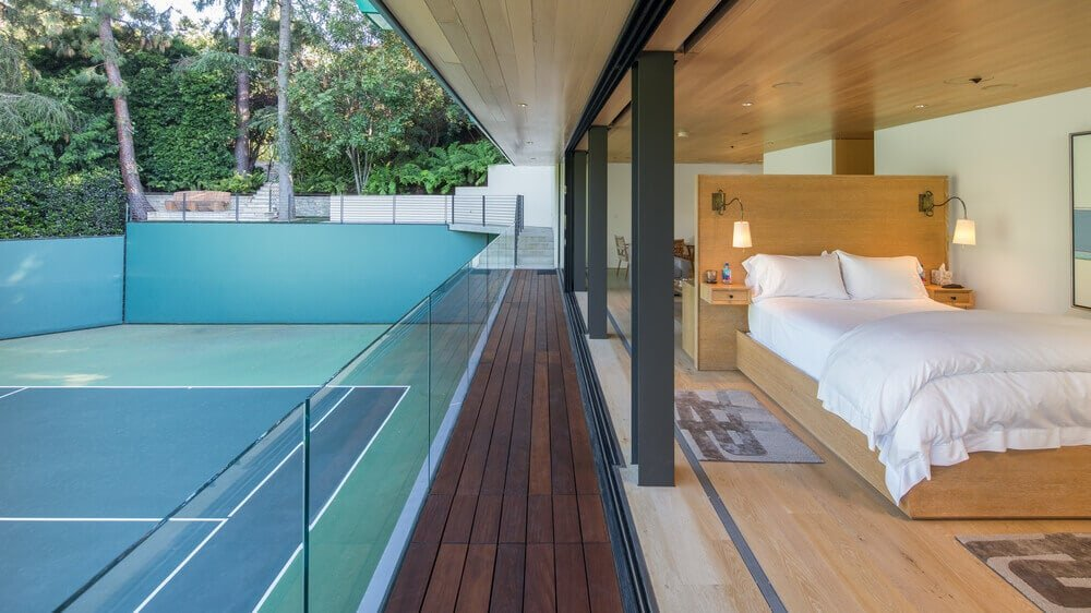 The house has a large tennis court with a second level viewing deck just outside the glass walls of the bedroom. Images courtesy of Toptenrealestatedeals.com.