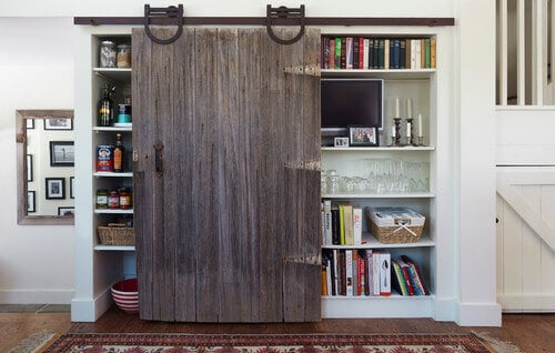 A single rustic sliding barn door may not cover all of this kitchen's shelving, but it does cover one side or another depending on which side is in use.