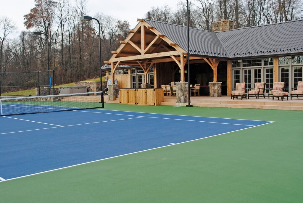 Here is a lovely tennis court with a high end pavilion with seating and glass doors. This is the perfect place to host many games of tennis. Anyone would be lucky to play a few games on a court like this.