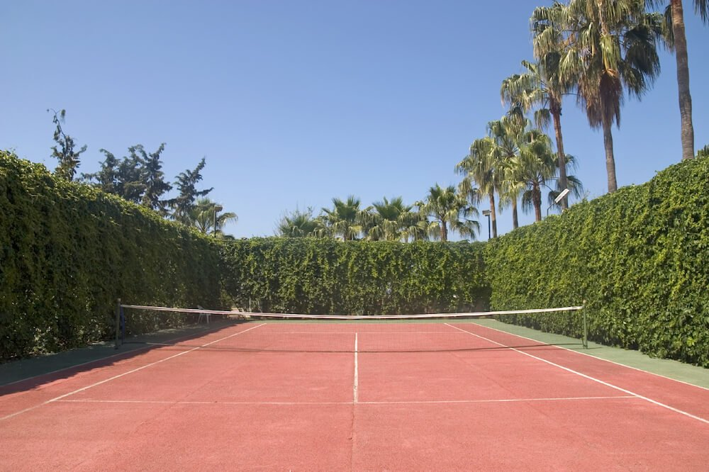Red clay tennis court rimmed by tall hedges, which are much more attractive than chain link!