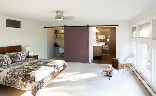 This primary bedroom and its dusky plum barn door shows the versatility of the door. When both the bathroom and desk areas need to be open, the door can rest in the middle of the wall between the two rooms.