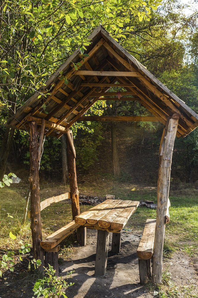 This small pavilion is built from raw wood and found lumber. The benches are built into the sides of the pavilion with a table in the center. This pavilion is only big enough to cover the few people sitting here, but that is as big as it needs to be. This is a great pavilion table for getting back to nature.