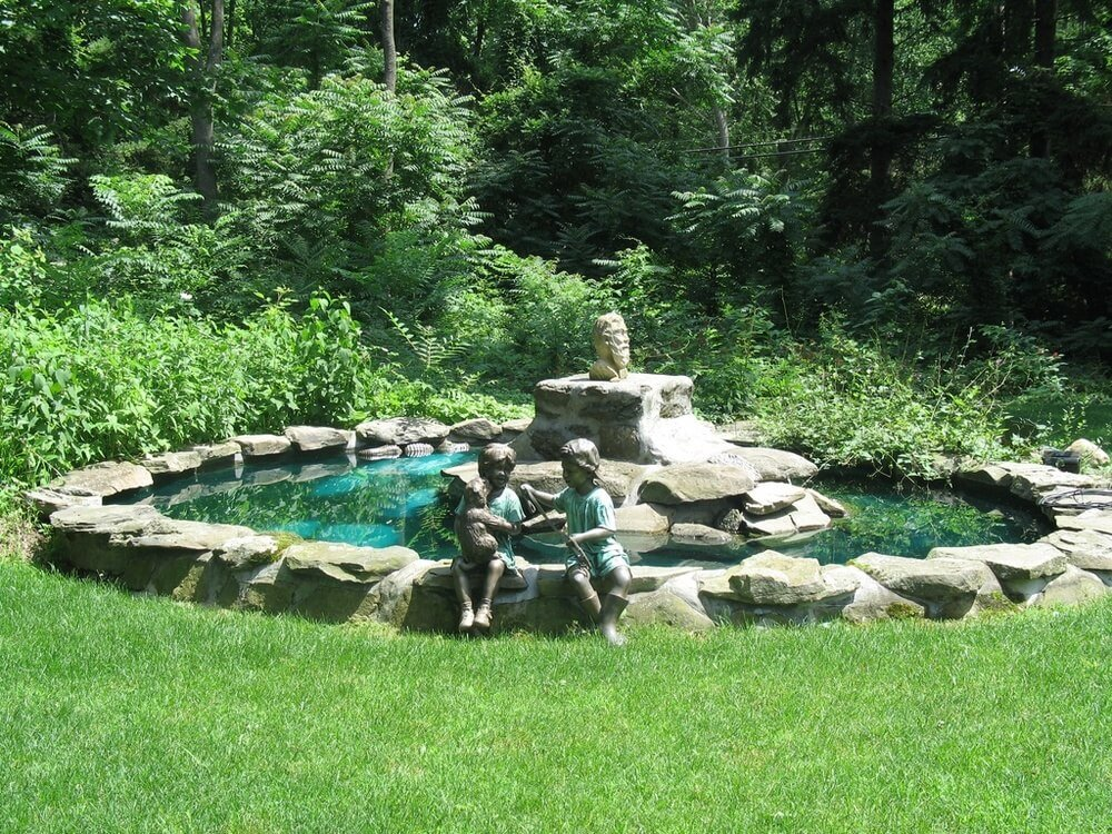 Sculptures of people are a very popular option for many. Placing a few sculptures of people around an area can make the space feel more full. These sculptures of children sitting by this pond make the space appear occupied and lively.