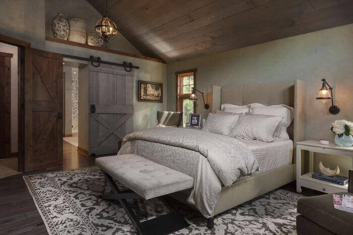 While much of the furniture in this primary bedroom is contemporary, the wooden ceiling and rustic sliding barn door adds rustic flavor. The orb-like light fixture is another great touch