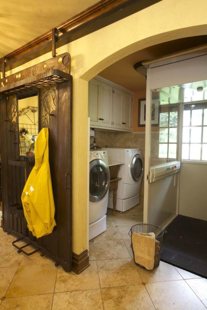 """This incredible """"barn"""" door may not be entirely made out of wood, but the sliding hardware allows it to serve the same function as more traditional examples of the style. This door is outfitted with lovely carvings and places to hang coats. The door can be slid in front of the laundry room to hide any messes."""