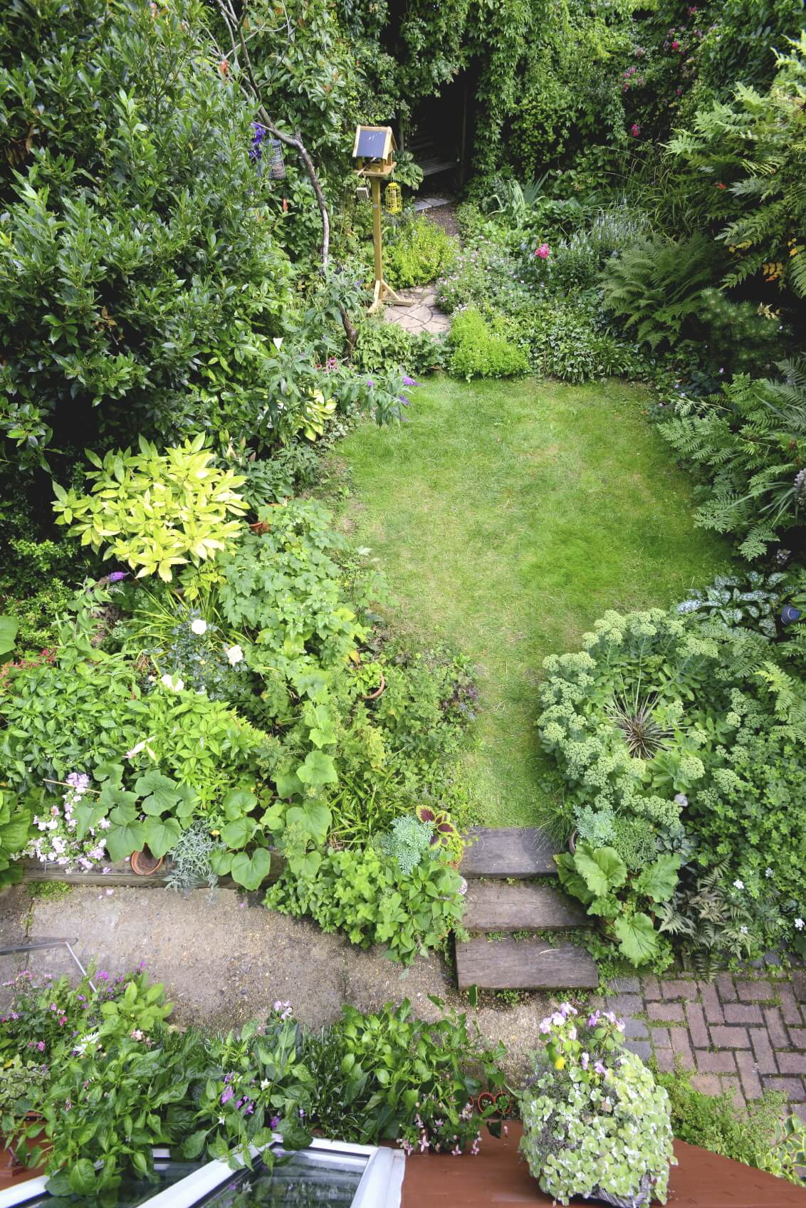 This yard has a small manicured lawn that has been surrounded by lush plant gardens. The plants have been left to run wild and appear to be swallowing the lawn area. This design makes it look as though the lawn has been carved out of the wilds of nature.