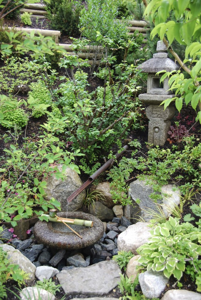 Rocks and stones are often used in Asian inspired landscaping. Here we can see a traditional Japanese water feature in a small hidden rock garden. This is a wonderful place to go and meditate among nature with the soothing sound of running water.