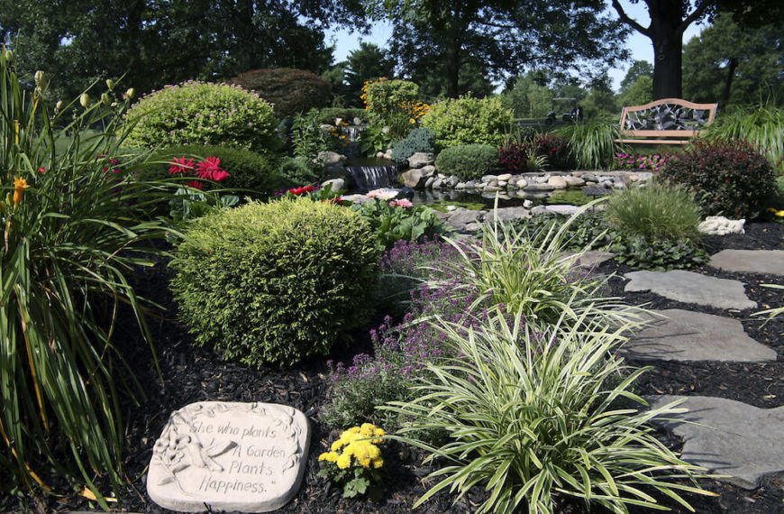 In this picture there is a bench on the far end of a shrub garden. This is a classic bench that is attractive to anyone looking to sit out in the garden and enjoy nature.