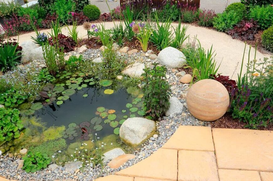 A small pond is a great accompaniment to a rock garden. Rocks look perfect around a small pond and work to transition the natural look of the pond into the masonry of the walkway.