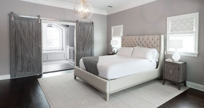 This is another beautiful example of a contemporary bedroom matched with more rustic sliding barn doors. These doors are in a rich gray and heavily textured.
