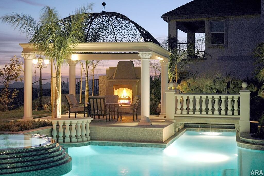 Here is an interesting pavilion with stone pillars and a designer canopy. This kind of top is not meant to keep rain off; rather, it is used as a design element. This pavilion makes this poolside fireplace an amazingly elegant place to spend a cool evening.