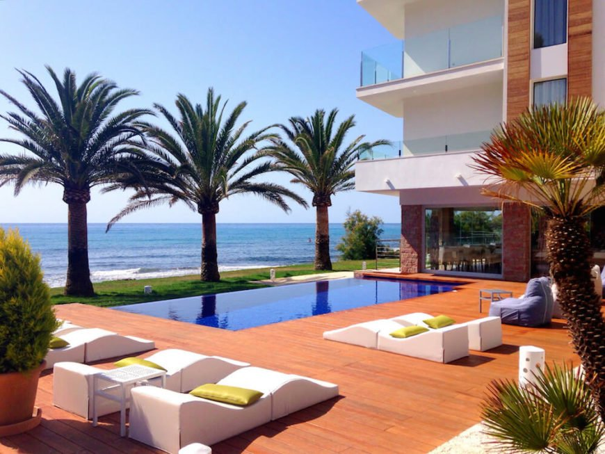 Palms can be used to divide a space without being too intrusive or becoming a barrier. Here are three lovely palms between a deck with a pool and the beachfront. The trees separate this area into two spaces but do not restrict movement between them.