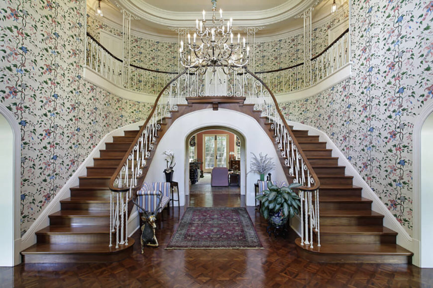 Double staircase in a wallpapered front hall complete with a chandelier.