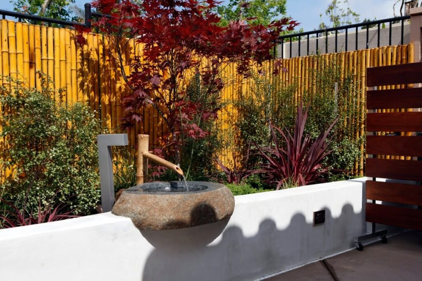 A bamboo privacy fence mounted on a wrought iron fence.