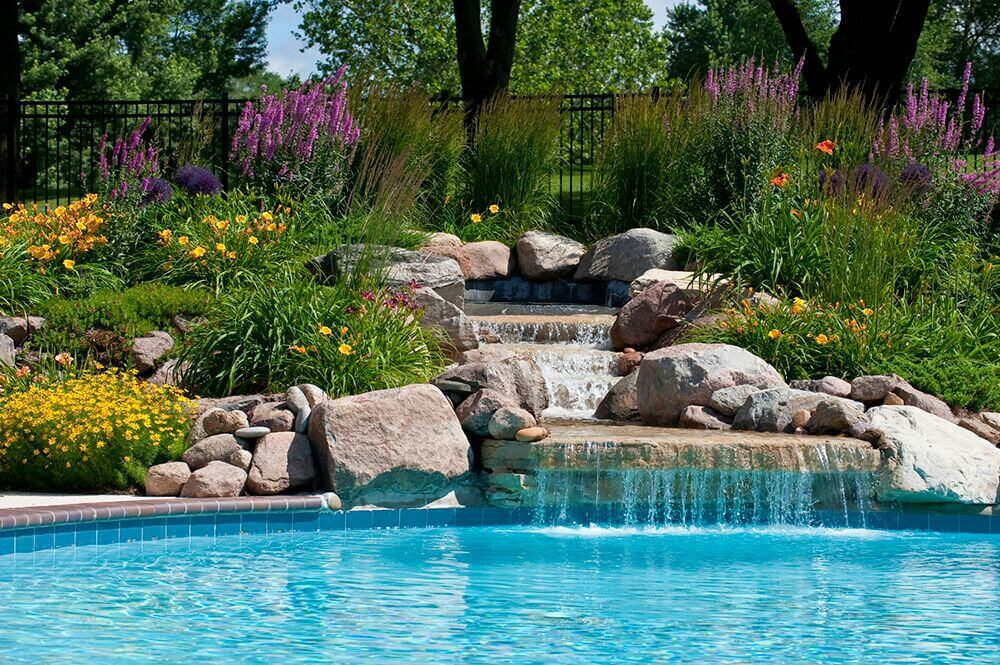 This pool and water feature has a number of perennial bushes to bring a touch of vibrancy to the manmade fixtures.