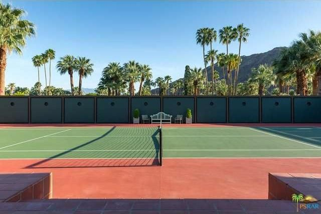 This is the tennis court that has tall concrete walls and a background of tall palm trees. Image courtesy of Toptenrealestatedeals.com.