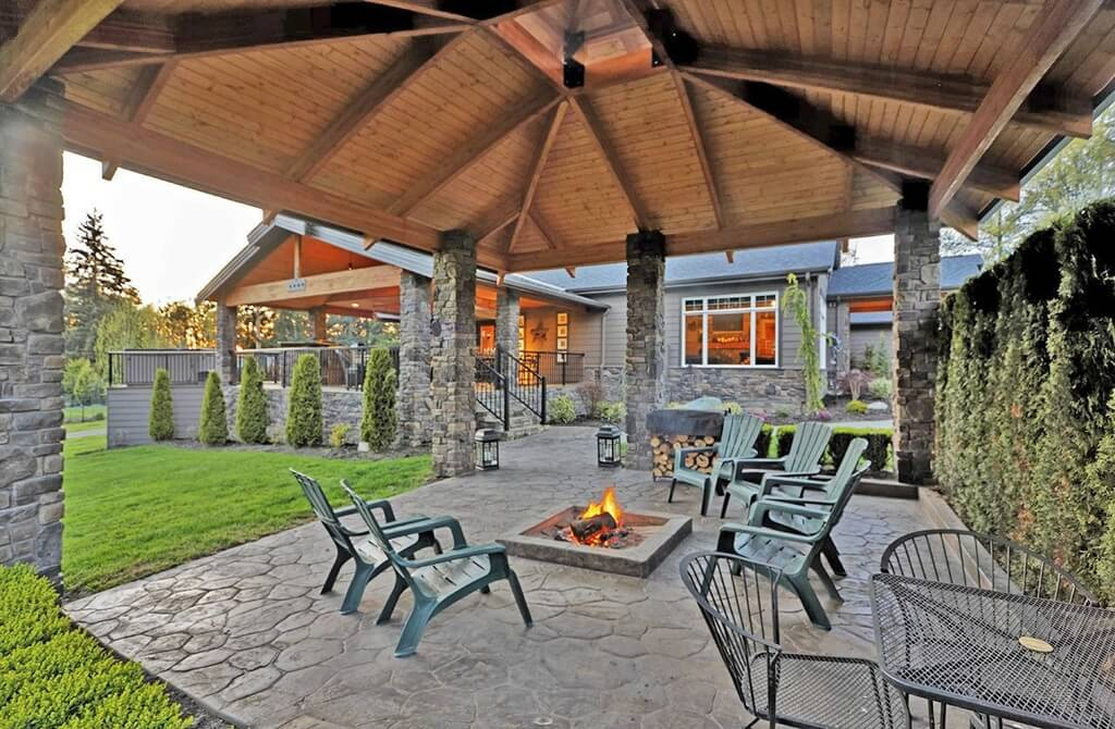 Stone pillars match stone walkways and other masonry structures. This pavilion has a very rugged and sturdy construction that blends with the stone patio and fireplace.
