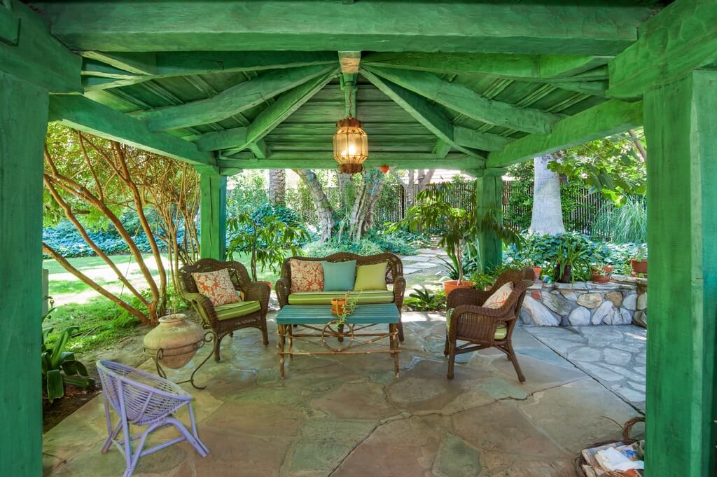Since wood is so versatile you can paint a wooden pavilion any way you choose. In this picture we see a wooden pavilion painted green. This color sets a tone for the design and color palette of the yard furniture that sits underneath.