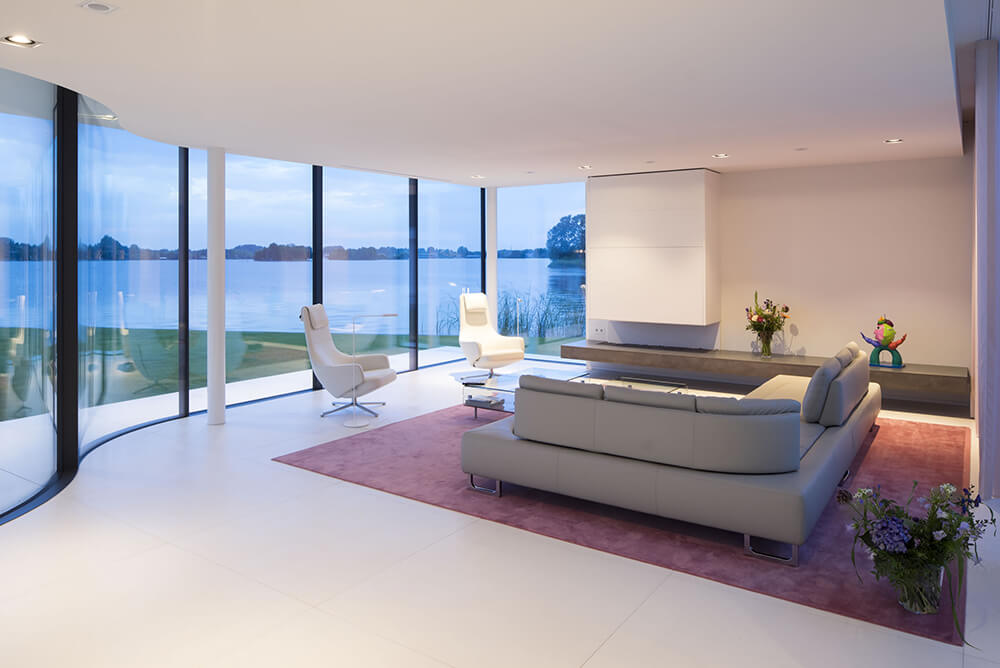 Modern living room with glass walls and windows together with cozy seats and stylish rug set on the tiles flooring.
