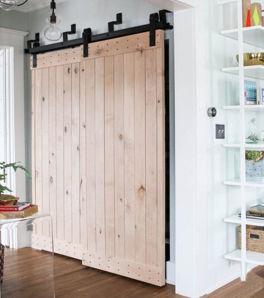 Simple light wood barn doors can be used in place of closet doors in an entry hall as well. The vertical boards add length to the space, and chunky black hardware adds industrial flair.