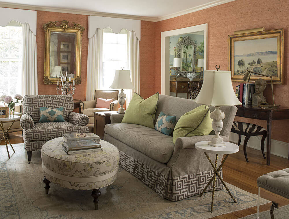 Decorative living room with textured orange walls, a gray cozy sofa, a printed mid-century armchair, an upholstered round center table, classic rug, and crafty decor pieces.