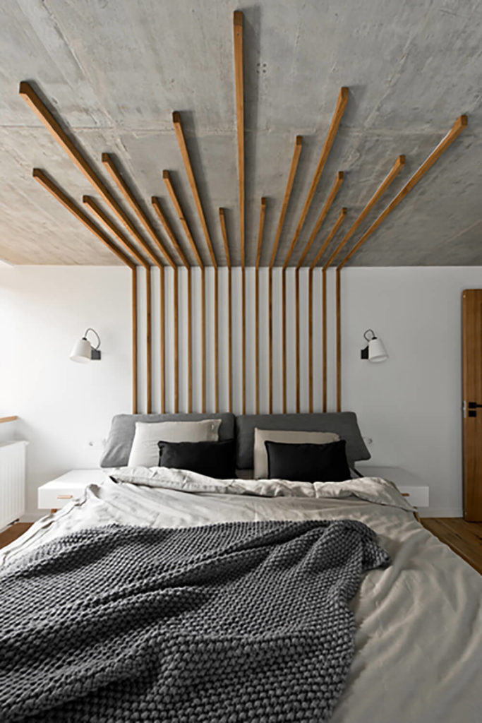 The primary bedroom is accented with another unique instance of thin natural wood slats, extending from a pseudo-headboard design across the ceiling. This wraps the entire room into a practical work of art.