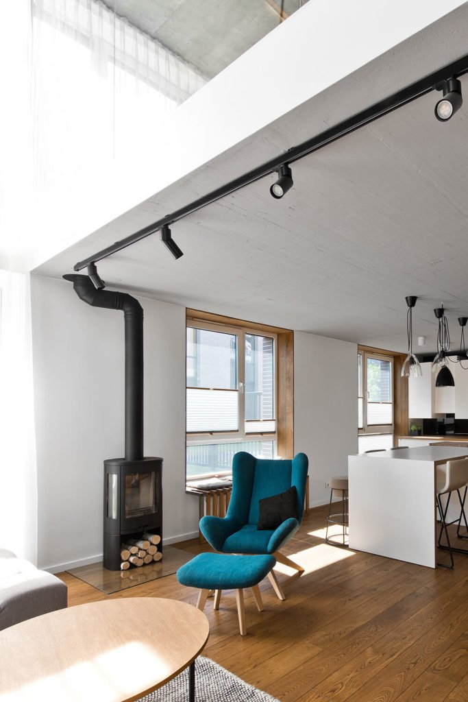 The home features a modern take on the traditional wood burning stove, parked on a glass platform near the window. The singular blue chair and matching ottoman create a subtle eruption in the neutral palette of the space.