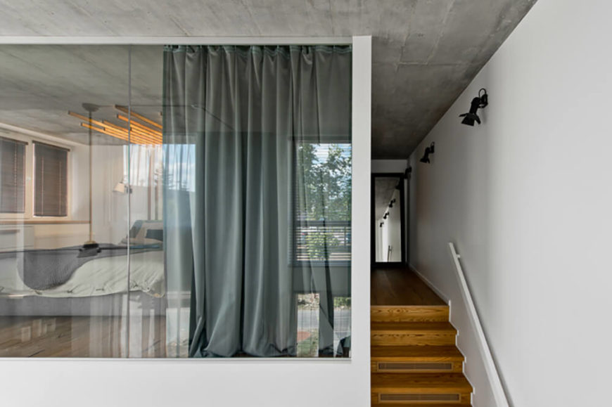 The upper level can be seen down the lengthy hallway at the top of the stairs, and right through the full heigh glass panels surrounding the primary bedroom, at left.