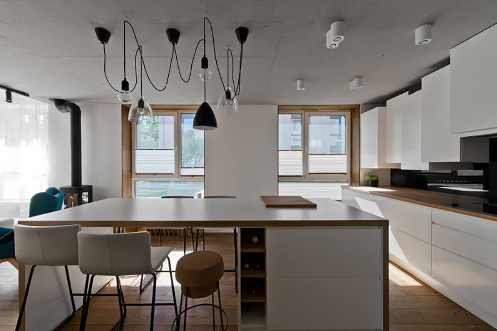 A modish Scandinavian-Style kitchen with a glamorous set of ceiling lights. The hardwood flooring matches the countertops on both kitchen counters and center island.