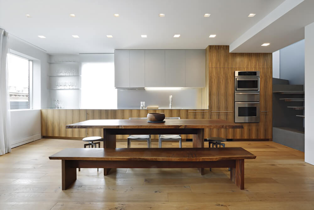 Simple kitchen with natural wood and white cabinets, floating shelves and stainless steel double ovens facing the wooden rectangular dining table and illuminated by square recessed lighting.