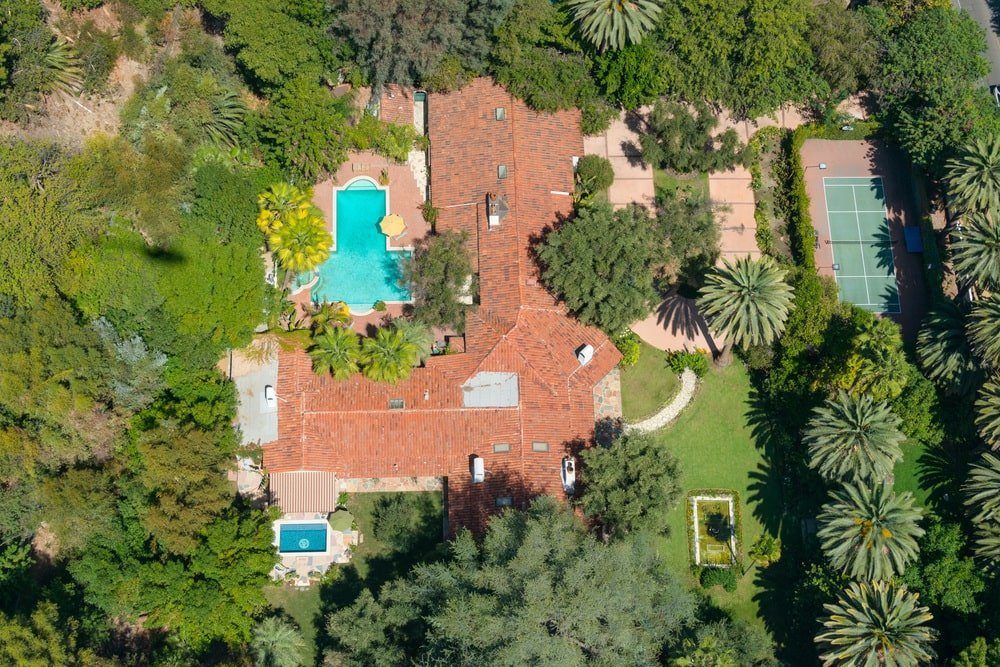 This is an aerial view of the whole property showcasing the different outdoor areas like the pools and the large tennis court at the side of the house surrounded by tall trees. Image courtesy of Toptenrealestatedeals.com.