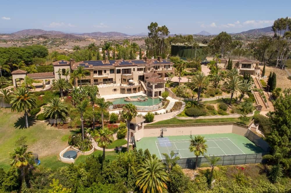 This aerial view of the property showcases the lovely tennis court at the back of the house by the pool. This is surrounded by hedges and tall trees. Images courtesy of Toptenrealestatedeals.com.