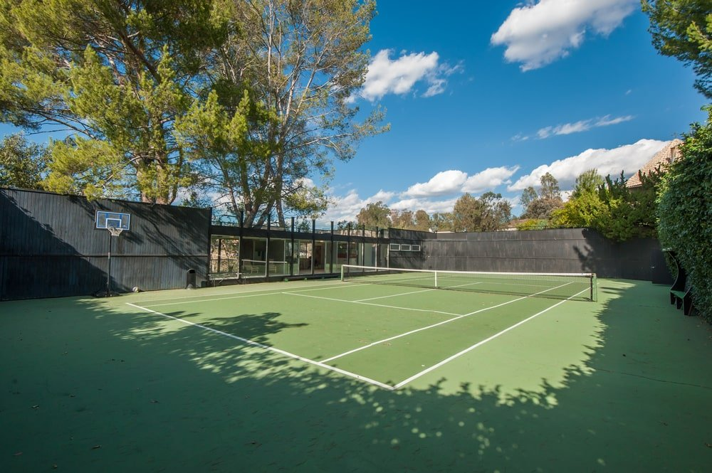 This is the professional-size tennis court with a green floor to make the white lines stand out. These are then complemented by the surrounding tall trees and walls. Image courtesy of Toptenrealestatedeals.com.