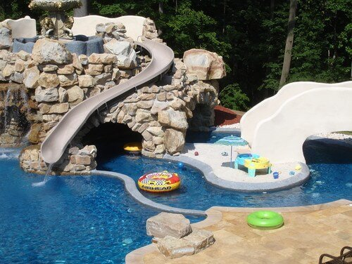 Here we see a water slide placed along a castle-esque stone structure in this water park area. Water slides are the quintessential feature of a water park. They can provide hours of fun and are by far the best way to get into the pool.