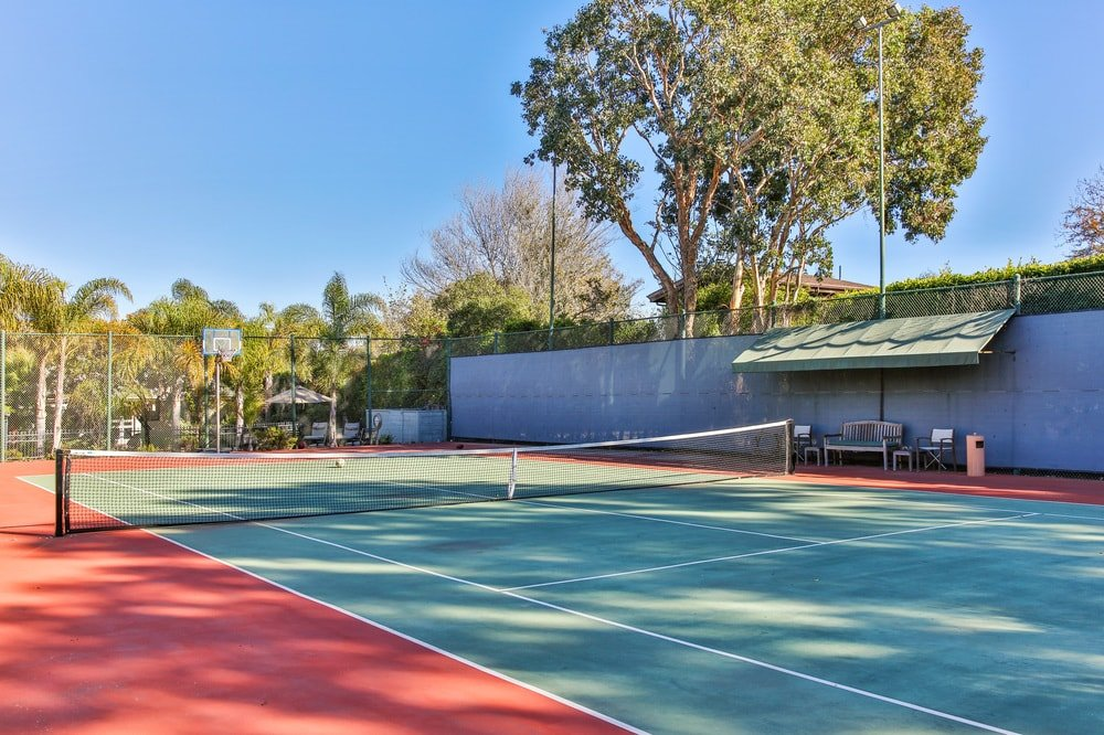 This is the large tennis court of the property with bright colors to its flooring that contrasts the lush mature trees surrounding the area. Image courtesy of Toptenrealestatedeals.com.