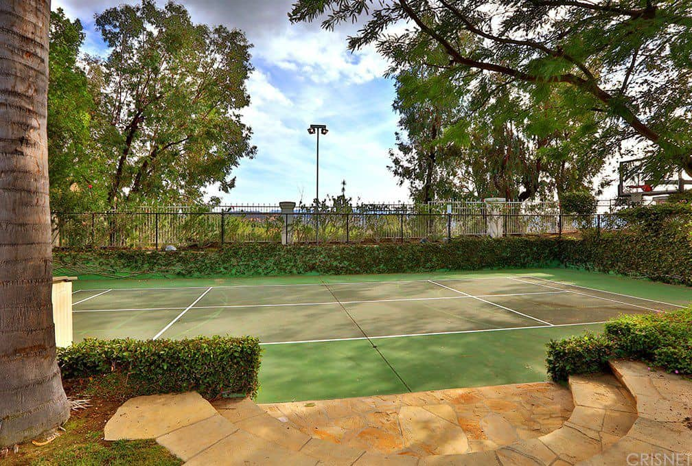 There is a stone path that leads to this beautiful tennis court that doubles as a basketball court. It is surroiunded by charming hedges of shrubs and tall trees.