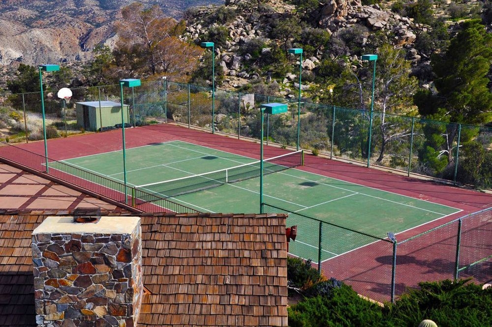 This is a focused look at the tennis court situated on the side of the swimming pool area surrounded by rocky views. Image courtesy of Toptenrealestatedeals.com.