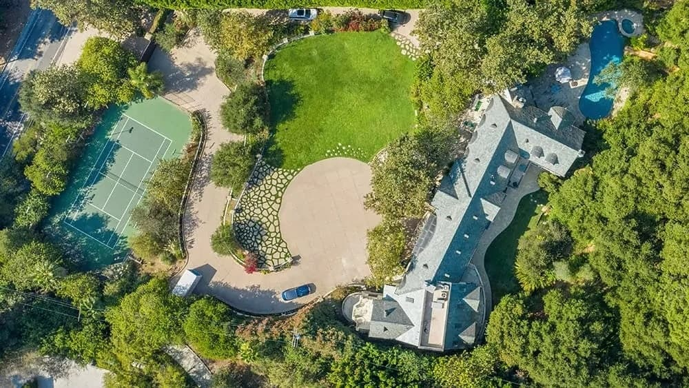 This is an aerial view of the whole property that has a large mansion on one side, a winding driveway and a tennis court surrounded by tall trees. Image courtesy of Toptenrealestatedeals.com.