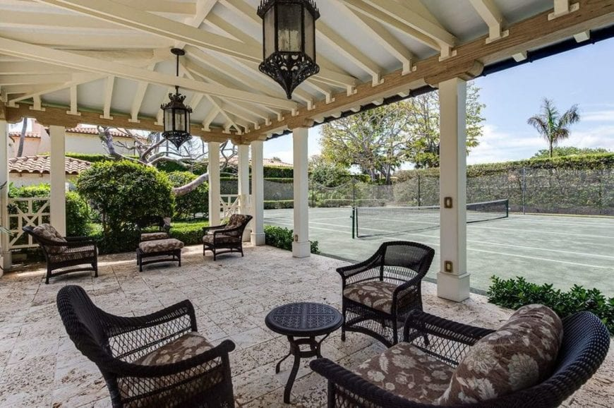 This is the covered patio right beside the tennis court that has a green tone to it. This covered patio is fitted with various cushioned chairs paired with lantern pendant lights. Image courtesy of Toptenrealestatedeals.com.