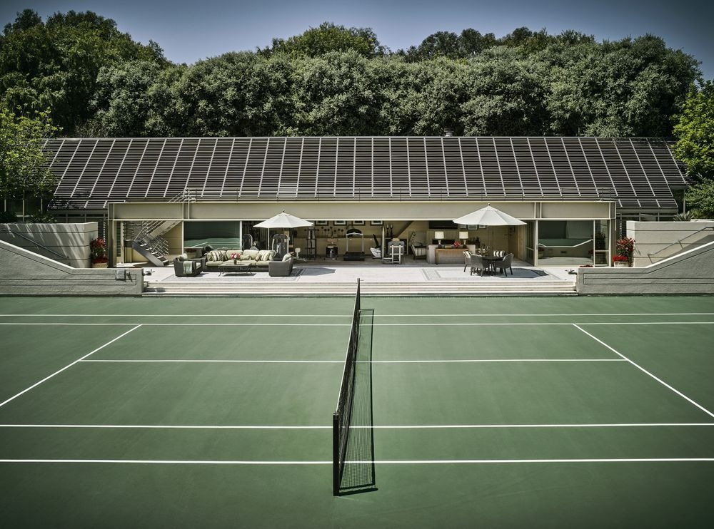 This is the tennis court inside the property. It has a green court with white lines paired with an open patio area and a background of tall trees. Image courtesy of Toptenrealestatedeals.com.