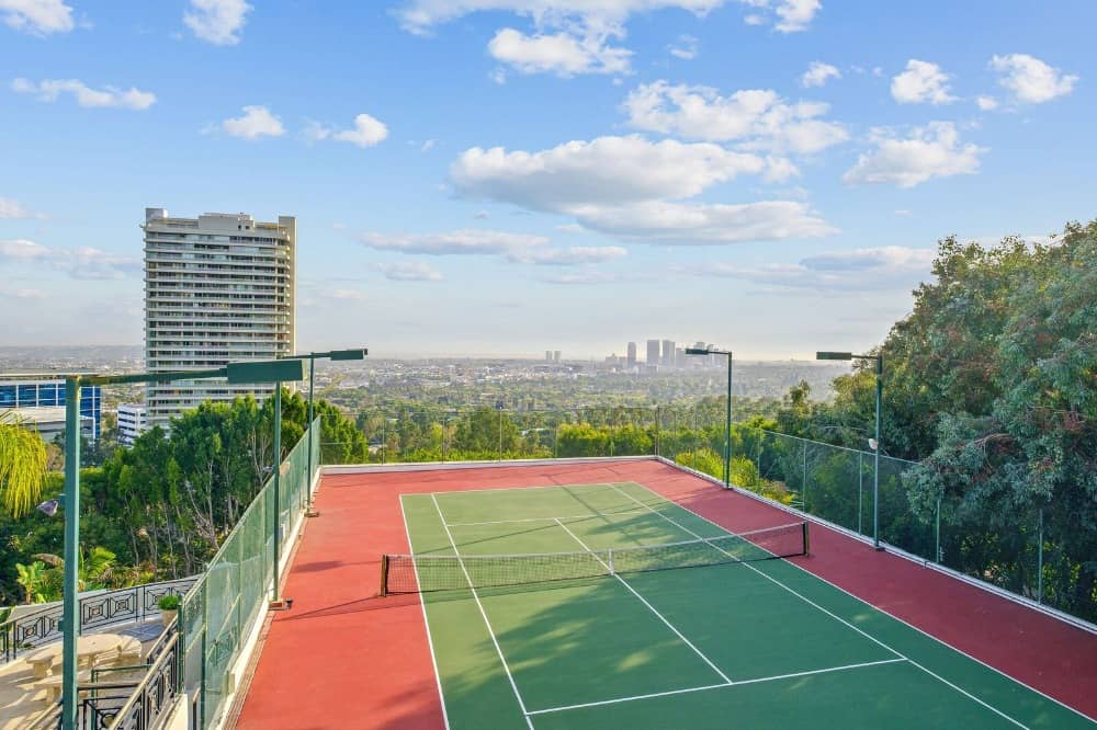 This is the rooftop tennis court of the mansion with fencing for safety and surrounded by professional outdoor lighting adorned by the tall trees and the view of the city skyline. Images courtesy of Toptenrealestatedeals.com.