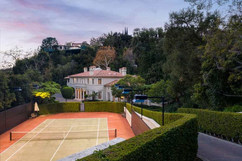 A few feet from the front of the mansion is the private tennis court which is enclosed by surrounding tall hedges that contrast the terracotta flooring that surrounds the court. Images courtesy of Toptenrealestatedeals.com.