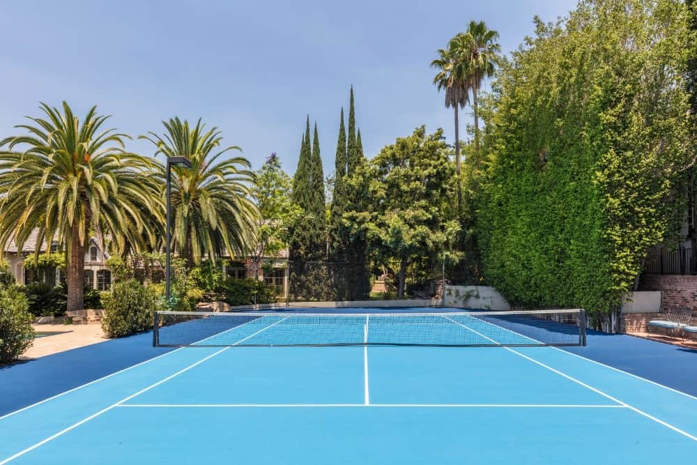 There is a beautiful blue tennis court at the back of the house adorned with tall tropical trees and shrubs that bring privacy and shade. Images courtesy of Toptenrealestatedeals.com.
